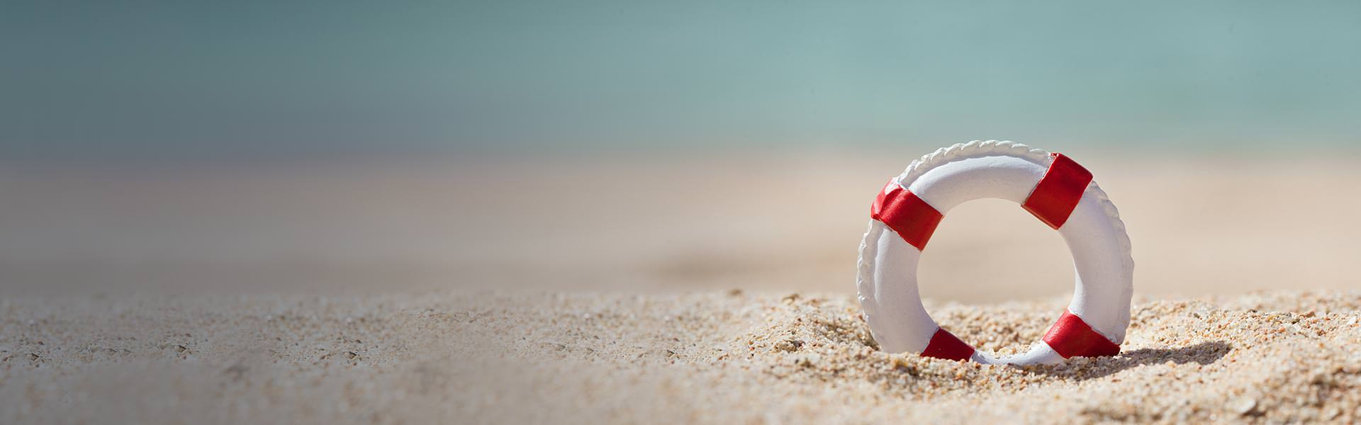 White And Red Lifebuoy Ring On The Beach Offer Help And Support
