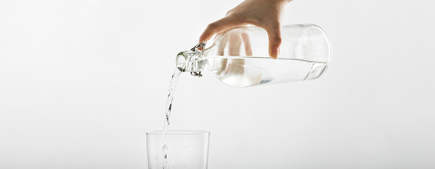 Person Pouring Natural Mineral Or Tap Water From Clear Bottle In Glass Hydration Water Drinking