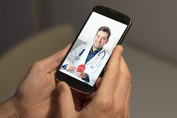 Personal Holding Phone Video Chatting With Doctor
