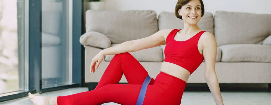 Young Woman Wearing Red Tracksuit Exercising Indoors Smiling