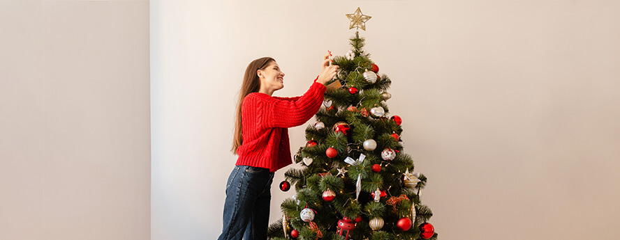 Young Girl With Long Hair Wearing Red Jumper Is Decorating Christmas Tree